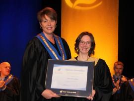La présidente du conseil d'administration, Caroline Gauthier, remet un diplôme honorifique à Marie Beauséjour.
