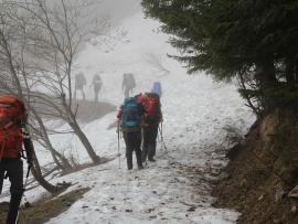 Des randonneurs dans la brume sur un sentier enneigé