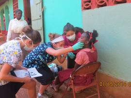 Des femmes avec un masque sanitaire examine la dentition d'une jeune fille