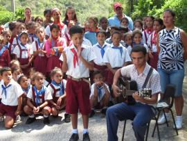 Des enfants costumés à Cuba écoutent un guitariste