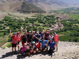 Des randonneurs au sommet d'une montagne avec vue sur un village