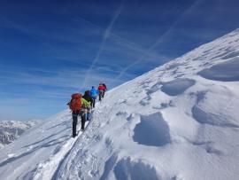 Des randonneurs grimpent sur une montagne enneigée
