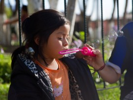 Un enfant souffle dans une machine à bulles